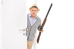 Senior with rifle bursting through a door Stock Photography