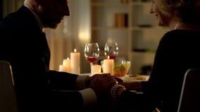 Senior romantic couple enjoying dinner in restaurant, grandparents holding hands stock photography