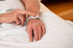 Senior with rufhilfe emergency phone in bed Royalty Free Stock Photos