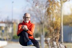 Senior runner man sitting after jogging royalty free stock photo
