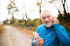 Senior runner in nature with smart phone with earphones. Senior runner in nature. Man with smart phone with earphones. Listening music or using a fitness app Stock Photo