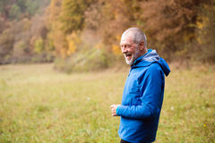 Senior runner resting outside in sunny autumn nature. Stock Photo