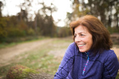 Senior runner sitting on wooden logs, woman resting, smiling. Royalty Free Stock Photography