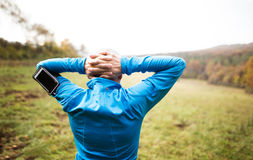 Senior runner with smartphone doing stretching. Autumn nature. Senior runner in sunny autumn nature doing stretching. Man with smart phone in armband on his arm stock photos