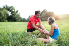 Senior runners in green field. Woman with injured knee. Stock Images