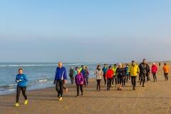 Senior runners on sandy beach stock photo