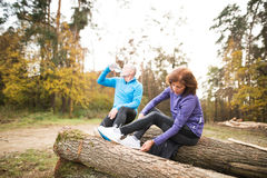 Senior runners sitting on wooden logs, resting, drinking water. Royalty Free Stock Photography