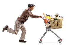 Senior running and pushing a shopping cart full of groceries Royalty Free Stock Images