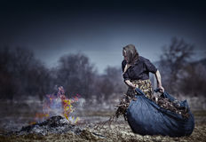 Senior rural woman burning fallen leaves Stock Photos