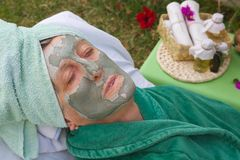 A senior's face is covered by clay facial mask.Close up Royalty Free Stock Photos