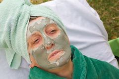 A senior's face is covered by clay facial mask.Close up Stock Photos