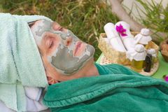 A senior's face is covered by clay facial mask.Close up Stock Image