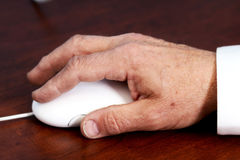 Senior's hand on mouse. Elderly hand using a computer mouse on a desk Stock Images