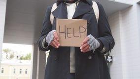 Senior sad man without shelter with cardboard sign HELP