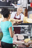 Senior Salesman Giving Cheese To Female Customer. Smiling senior salesman giving cheese to female customer at grocery shop Stock Photos