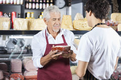 Senior Salesman Holding Cheese While Looking At Colleague Stock Photo