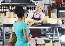 Senior Salesman Selling Cheese To Female Customer. Smiling senior salesman selling cheese to female customer at grocery shop Royalty Free Stock Photography