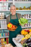 Senior Salesman Selling Vegetables In Supermarket Stock Photo