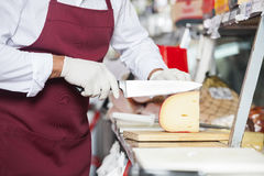 Senior Salesman Slicing Cheese In Shop Royalty Free Stock Images
