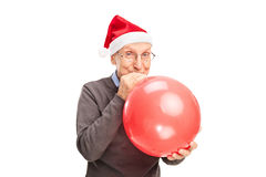 Senior with Santa hat blowing up a balloon Royalty Free Stock Images