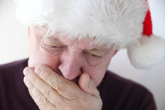 Senior in Santa hat has nausea Royalty Free Stock Image