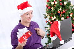 Senior santa holding present and using a computer Royalty Free Stock Images