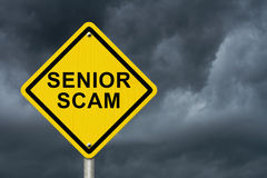 Senior Scam Warning Sign. An road warning sign with words Senior Scam with stormy sky background Royalty Free Stock Photography