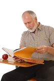 Senior in school. Older gentleman back in school at a desk with a textbook Royalty Free Stock Photography