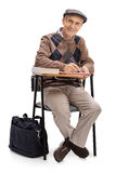 Senior in a school chair taking notes. And looking at the camera isolated on white background Royalty Free Stock Photos
