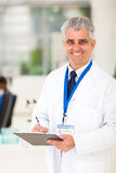 Senior scientist lab. Smiling senior scientist writing on clipboard in lab Royalty Free Stock Images
