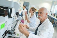 Senior scientist looking at slide at laboratory. Senior scientist looking at slide at the laboratory Royalty Free Stock Images