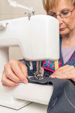 Senior seamstress woman working on sewing machine Royalty Free Stock Photography
