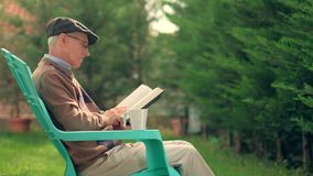 Senior seated in a plastic chair reading a book outdoors. Senior seated in a plastic chair reading a book and drinking from a cup outdoors stock video