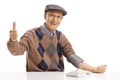 Senior seated at a table measuring his blood pressure and making royalty free stock images
