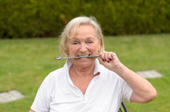 Senior serene woman biting on a wrench Royalty Free Stock Photo