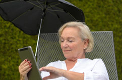 Senior serene woman using a black tablet PC Stock Photography