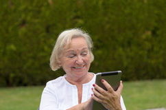 Senior serene woman using a black tablet PC Royalty Free Stock Photos