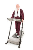 Senior Serious About Fitness. Senior man on treadmill is serious about fitness.  Isolated on white Royalty Free Stock Images