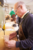 Senior shoemaker shaping shoe lasts in a workshop Stock Photography