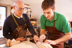 Senior shoemaker training apprentice to make shoe lasts Stock Images
