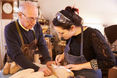 Senior shoemaker training apprentice to make shoe lasts Royalty Free Stock Image
