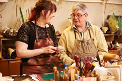 Senior shoemaker training apprentice to work with leather Stock Photo