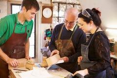 Senior shoemaker training apprentices to make shoe lasts Royalty Free Stock Image