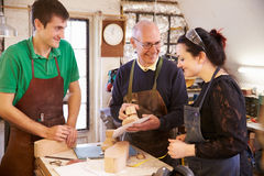 Senior shoemaker training apprentices to make shoe lasts Stock Photos