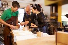 Senior shoemaker training apprentices to make shoe lasts Stock Image