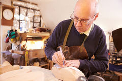 Senior shoemaker working in a workshop Royalty Free Stock Image