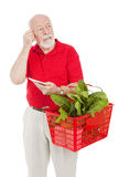 Senior Shopper - Forgetful. Senior man shopping for groceries has forgotten what's on his list.  Isolated on white Royalty Free Stock Images