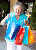 Senior Shopper Inspects Bags Stock Photography