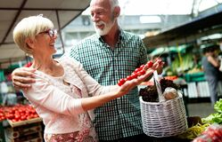 Mature shopping couple with basket on the market. Healthy diet. Senior shopping couple with basket on the market. Healthy diet
