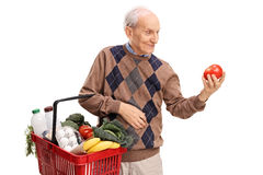 Senior shopping and looking at a tomato Stock Image